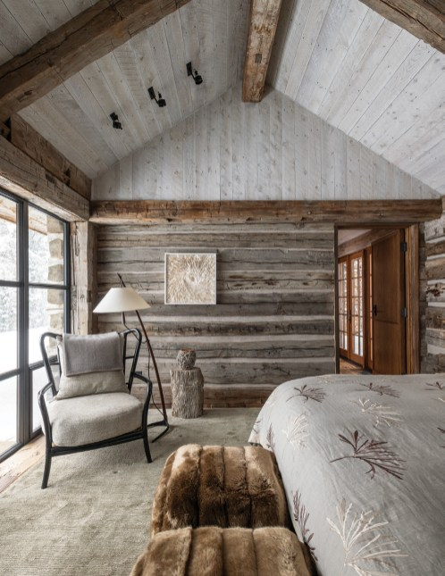 The homeowners' bedroom was constructed from a reclaimed cabin and features a chair from McGuire Furniture upholstered in Laura Lienhard fabric, artwork by Rakuko Naito, and a petrified log stump, sourced from Susanne Hollis Antiques, that makes for a sturdy end table.