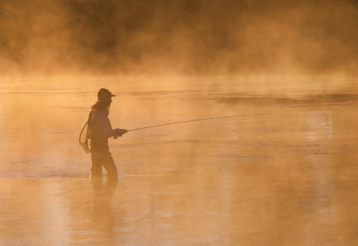 """Morning mist envelops Emily Gribble as she fishes Yellowstone's Firehole River. """"I like the ethereal feeling the mist provides and having the scene backlit, which adds color and emphasizes the outline of the angler, her rod, hat, and net,"""" Juracek says."""
