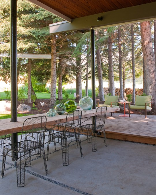 Patio dining is enhanced by a table made from one slab of wood and wire mesh chairs that create a sense of transparency allowing for unobstructed views; also in this photo: in the far right, three-legged lounge chairs are by Don Harding.