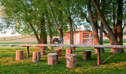 """Gathering under an umbrella of trees and a view of the barn beg for parties en plein air. the dining table and """"chairs"""" made of tree stumps add to the charm of this outdoor room."""