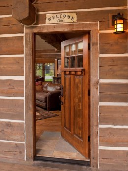 A modest front door makes for an understated entrance to the cabin's vaulted great room.