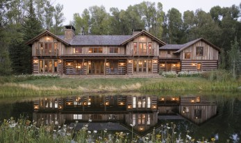 Embracing the homeowners' love of traditional mountain log homes, architect John Carney designed this lodge with hand-hewn chinked logs on the lower level of the house, while integrating a contemporary vertical line on the second floor by using weathered