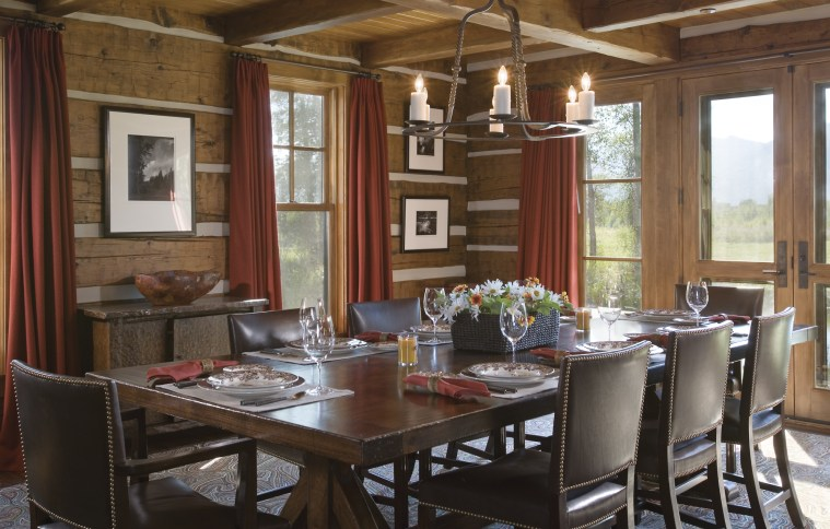 The formal dining room with coffered timber ceiling is decorated with the homeowners' black and white photography collection, offering balance to the saturated earth tones and natural materials of the interiors.