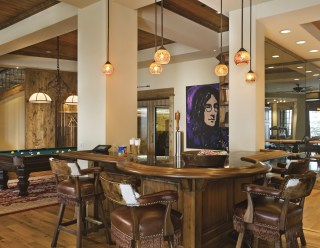 """Recessed lighting and a wall of windows on the ground floor with Western-inspired furnishings create a bright, fun atmosphere in the """"rec room."""""""