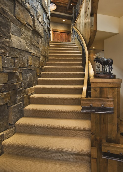 """A sculptural staircase, with a gracefully curved railing and hand-forged iron work, leads to the """"rec room"""" on the lower level."""