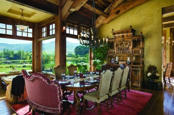 An ornate antique French armoire completes the dining room, bringing the focus indoors, while the scenic landscape outside remains an ever-present backdrop.