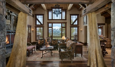 Massive splayed cedar columns frame the interior view of the great room and the distant vista of Beehive Basin outside.