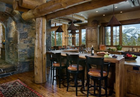 Views are prominent even in the kitchen, where large lodge pole pines serve as a trellis for the L-shaped kitchen island seating.