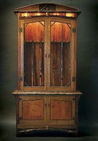 """""""Stick 'em Up!"""" Gun Cabinet This distinctive 12-gun case and pistol cabinet is entirely handmade with traditional joinery and old-school woodworking techniques. Additional details include hand-forged hinges, latches and locks, carved """"bark look"""" edging, and an intricate relief carving of two crossed shotguns with bagged quail. Backlit bark accent lighting showcases your gun collection. Made from Mulberry, Eucalyptus, Black Walnut, White Oak, Sycamore, Elm, Hand-forged Hinges and Latches, Lamb's Wool, Leather. 48""""W x 18""""D x 91""""H"""