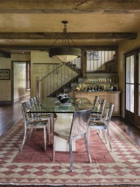 The dining room is a contemporary centerpiece with a custom-designed glass topped table, reflective Philippe Starck chairs, Harlequin-patterned rug contrasting the rustic timbers, wrought iron accents and the mottled hand-waxed plaster walls.