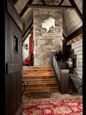 A rare mountain goat stands sentinel on the rock ledge over the foyer. The custom-built front door was constructed by Montana Sash and Door in addition to many features in the home.