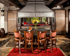 The custom-made zinc and steel strapped hood is a centerpiece in the massive kitchen, where sweeps of granite add a dynamic element to this working space.