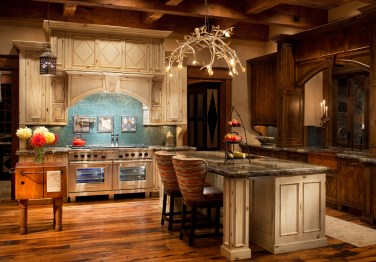 In the open kitchen a branch chandelier made by a Brazilian artist adds a sculptural element to the room. The blue glass tile backsplash links with the interior color palette.