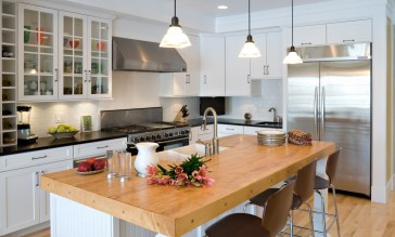 """Outfitted with custom cabinetry by Bozeman Kitchen and Bath, a six-burner, double oven Five-Star gas range, a 48"""" x 48"""" wide stainless refrigerator and central butcher block island, this kitchen is all about function."""