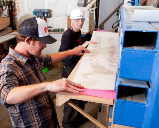Zak Anderson, left, of Montana Ski Company, and TJ Sneva line up base material and graphics on the sublimation press.