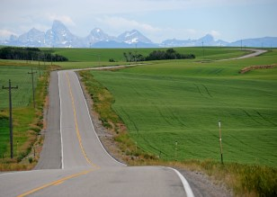 The long ribbon of road between Ashton, Idaho to Driggs is punctuated by the distant Teton Mountains. Photo by Will Brewster