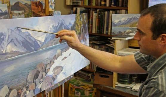 Elliott's studio is situated in a small cabin behind his Helena, Montana home. Older field studies tilt against the wall along a ledge. Paintings, finished and abandoned, stand on the floor and along the wainscoting for easy access. At the moment Elliott works only on this painting, giving it all his attention.