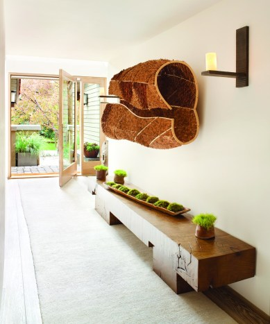 The quietly welcoming entrance hall is highlighted by a Minoru Ohira wood sculpture and bench from Mimi London.