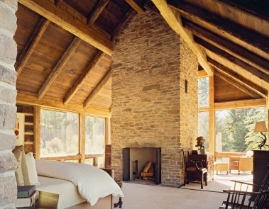 The airy master bedroom centers on a parged stone monolithic, mantel-less fireplace. Allowing the natural materials to show their character rather than adding too much detail was essential to this design. Photo: Matthew Millman Photography