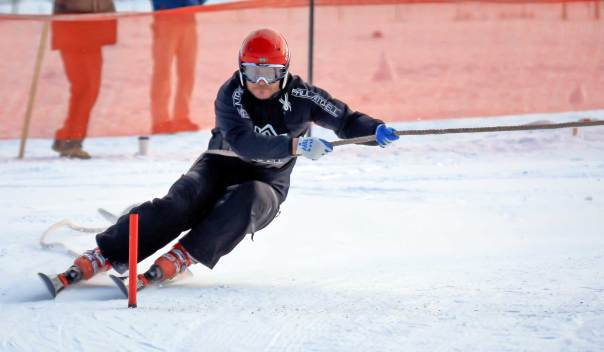A skier makes a tight turn around a slalom gate.