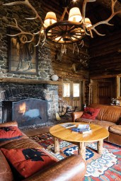 "Rustic elegance defines the Brooks Lake Lodge ""tearoom,"" where a fire burns regularly in a massive stone fireplace and classic wildlife mounts adorn the walls."