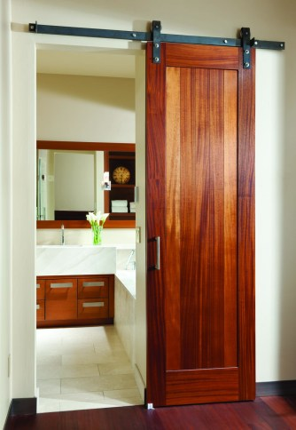 Custom-made sliding barn doors outfit the bathroom and guest suites in the lower level.