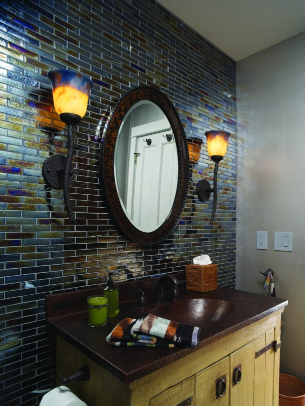 In the powder room, the hammered copper vanity compliments the earthy tones in a refined glass tiled wall.