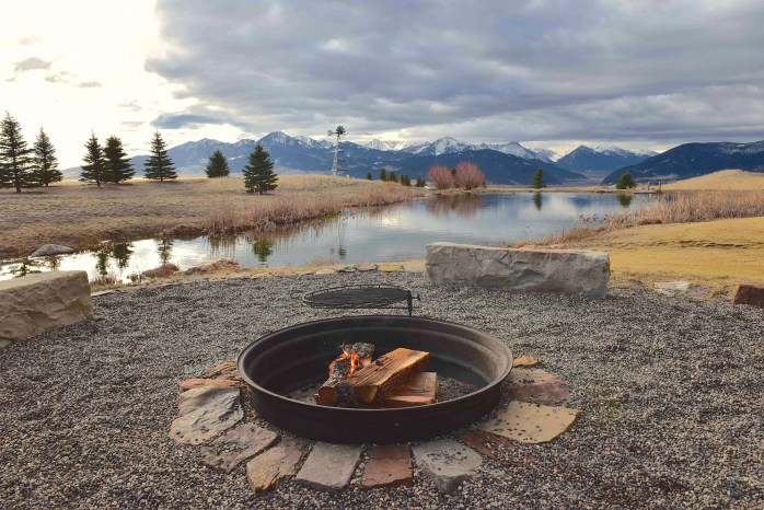 A backyard firepit enhances the Montana mystique, set on the edge of a trout pond looking toward Paradise Valley.