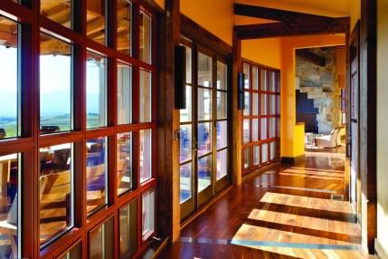 An entire hallway of windows opens toward the Bitterroot Range.