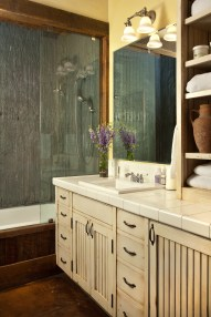 Opting for functional over fancy, the owners used rolled corrugated metal to line the shower, stained concrete floors in many places and painted wood cabinetry for accents.