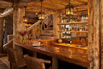The ground floor of the home wraps visitors in warmth, with a copper-topped bar in the saloon, which features a layered view of the juniper banister and the wine room in the background.