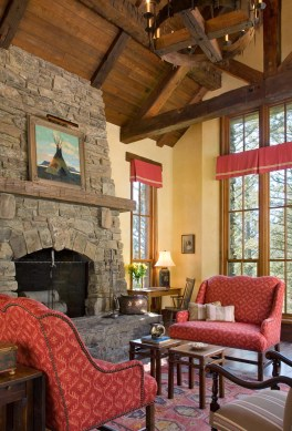 In the living room generous mullioned windows connect to the landscape and illuminate the interior spaces with natural light. A thoughtful art collection echoes the vibrant color palette of warm red, yellow, green and blue. Paying tribute to the region's Native American influence, a romantic tipi from Montana artist Tom Gilleon sits above the mantel.