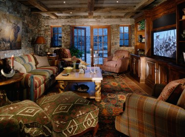 The TV room features lower ceilings, compressing the space to make it cozy and warm. Timber, stone and plaster offset the openness of the French doors and windows on both ends of the room. Photo courtesy perrenoudproductions.com