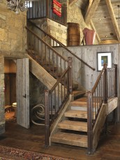A central staircase, adorned with a contemporary hand-forged iron railing, leads to a bunkroom.