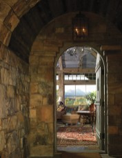 An arched doorway with Old World charm leads to layers of beauty with the Grand Tetons visible in the distance.