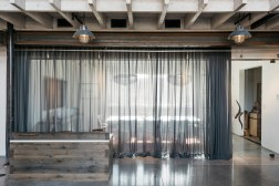 A privacy curtain is drawn across the glass-walled conference room where a picture window provides ample sunlight and views of passing trains.