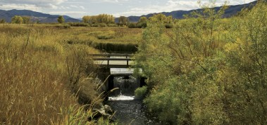 A rolling cylinder aerates water converging from the managed wetland into Clear Creek, a braid of the Ruby River.