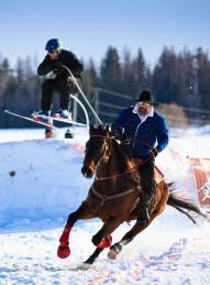 Skijoring organizer Scott Ping and his horse Kona Coffee pull skier Rob Alexander over one of three jumps on the U-shaped, 800-foot long course.