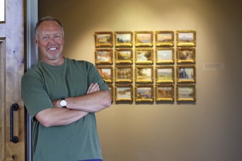 The artist stands before a wall of studies in his gallery.