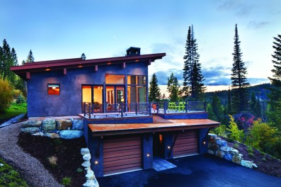 Built above a two-car garage and entryway, the ski chalet's main level glows in the twilight.