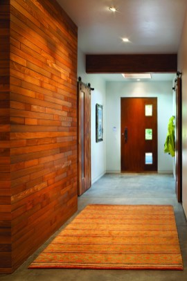 A one-of-a-kind wall and door constructed from reclaimed wood adds texture and warmth to the lower entryway.