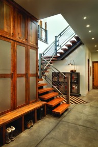 A stunning, industrial steel beam stairwell on the lower level leads to the main living area. Built-in cabinets provide an attractive place to store gear.
