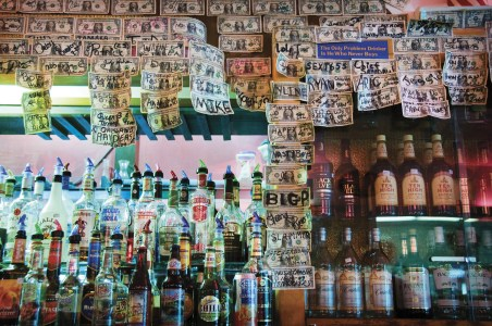 Dollar bills with black marked notes adorn the bar back of the Townsend Mint. Photo By: Tony Demin