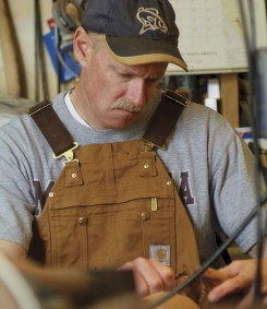 Artist Tom Dean carves a rainbow trout our of Hawaiian koa wood in his studio.
