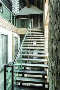 Reinforcing the element of transparency throughout the home, a glass and steel banister lines two levels of stairs.