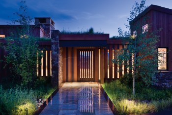 Wooden slats, backlit by the interior lighting, peak curiosity and ensure privacy.