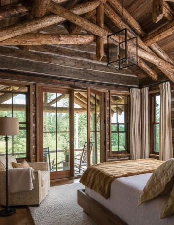 Exposed beams, full length windows and easy access to a deck transform this bedroom into a cabin-like aerie that makes the most of indoor-outdoor living.