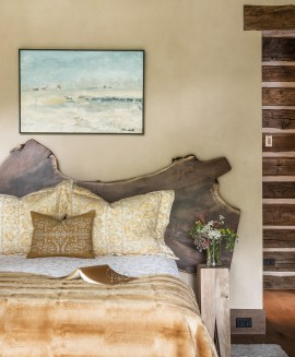 A live-edged rustic headboard — made by Brandner Design from an old-growth walnut tree from New York's Central Park — stands out against light walls and linens in the master bedroom.