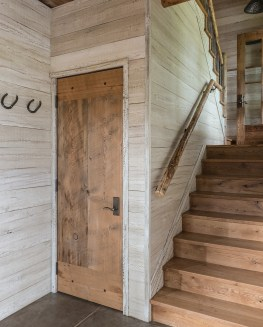 The guest barn entry features whitewashed walls, reclaimed oak flooring and custom interior doors.