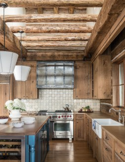 The kitchen is bathed in natural light, even on a cloudy day. Custom tiles adorn the backsplash while the handbuilt island features a walnut top and the owner's favorite blue color on its face.